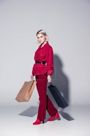 Foto de Chica atractiva moda en ropa de moda rojo con bolsas de compras, en gris - Imagen libre de derechos