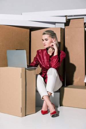 Photo for Beautiful fashionable girl using laptop while sitting on cardboard boxes - Royalty Free Image