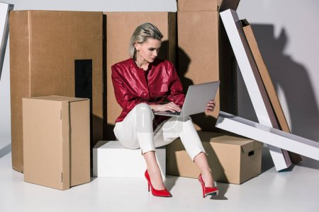 Photo for Attractive fashionable girl using laptop while sitting on cardboard boxes - Royalty Free Image
