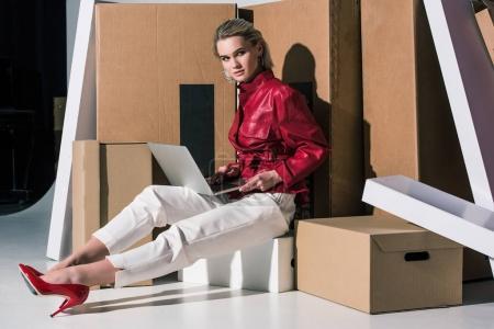 girl using laptop on boxes