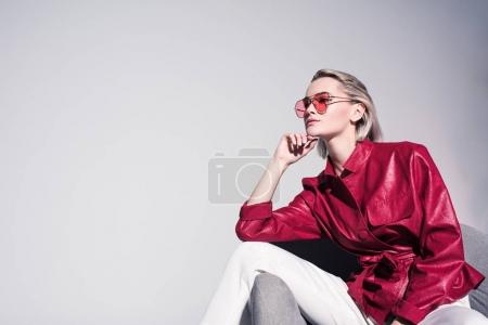 Photo for Attractive stylish girl posing on armchair for fashion shoot, isolated on grey - Royalty Free Image