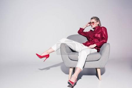 Photo for Attractive stylish girl posing on armchair for fashion shoot, on grey - Royalty Free Image