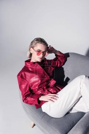 Foto de Chica elegante atractiva posando en el sillón para sesión de moda, aislado en gris - Imagen libre de derechos