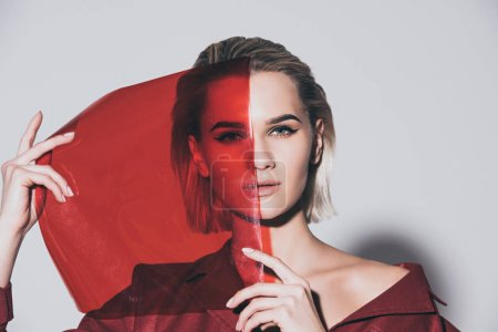 Photo pour Belle fille de style posant avec filtre rouge pour le tournage de mode, isolé sur gris - image libre de droit