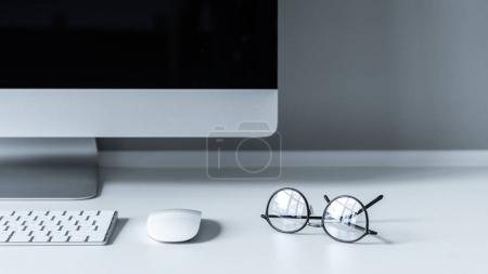 glasses with reflection on white working tabletop