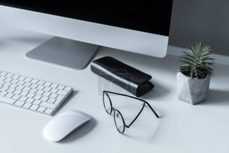 overhead view of glasses and spectacle case on working table