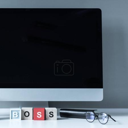 computer and wooden cubes with word Boss on a table