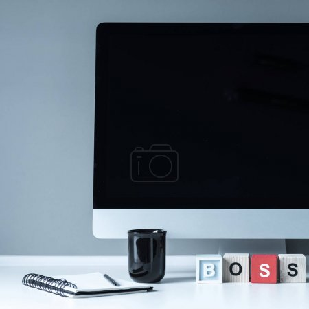 computer and wooden cubes with word Boss