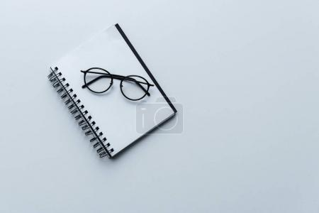 Photo for Top view of glasses on open white notebook isolated on white - Royalty Free Image
