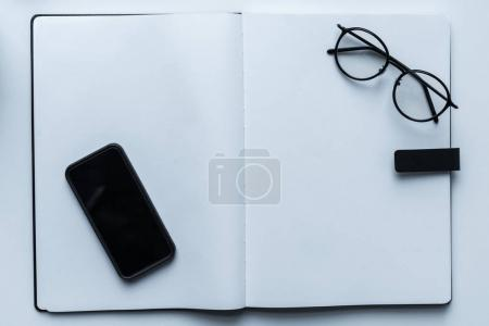 top view of smartphone and glasses on open notebook