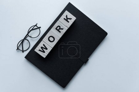 top view of black notebook and cubes with word Work