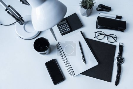 overhead view of working table with smartphone and notebook