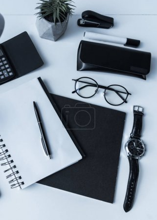 overhead view of notebook and pen with watch on working table