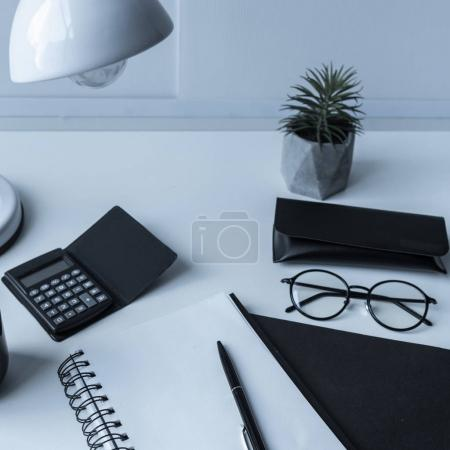 open notebook and pen with calculator and glasses on table