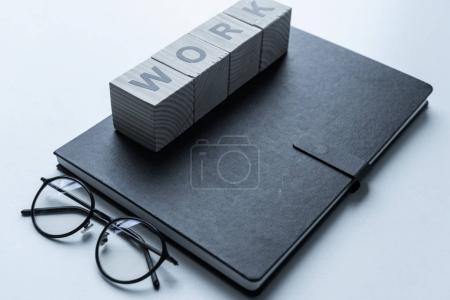 glasses and wooden cubes with word Work on black notebook