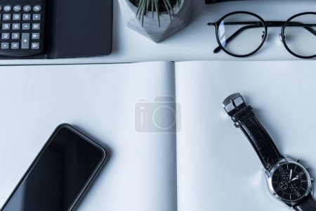 overhead view of smartphone and watch on open notebook