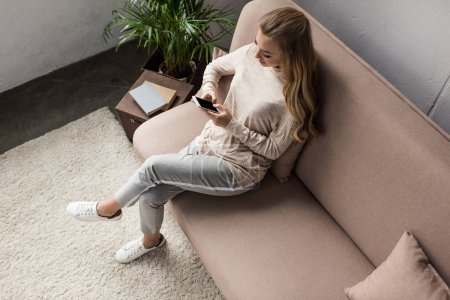 high angle view of young woman using smartphone while sitting on couch at home