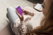 cropped shot of woman on couch using smartphone with instagram app on screen