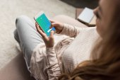 cropped shot of woman on couch using smartphone with twitter app on screen