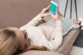 woman on couch using smartphone with twitter app on screen