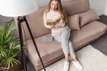 high angle view of young woman reading book on cozy couch at home