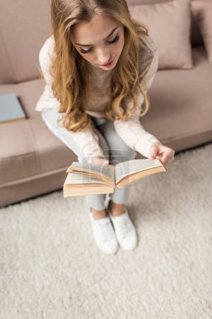 high angle view of beautiful young woman reading book on cozy couch at home