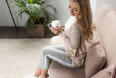beautiful young woman with cup of hot drink sitting on couch at home