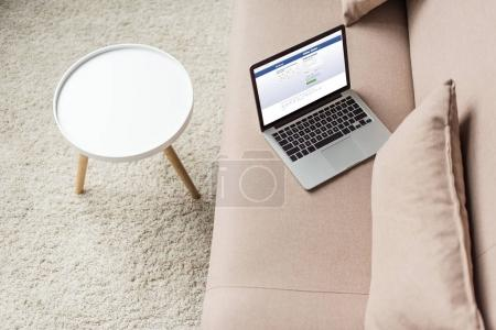 high angle view of laptop standing on cozy couch with facebook website on screen