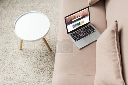 high angle view of laptop standing on cozy couch with shutterstock homepage website on screen