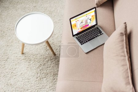 high angle view of laptop standing on cozy couch with aliexpress website on screen