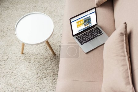 high angle view of laptop standing on cozy couch with booking website on screen