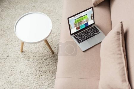 Photo for High angle view of laptop standing on cozy couch with bbc website on screen - Royalty Free Image