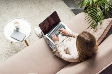 high angle view of young woman working with laptop at home