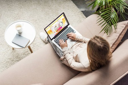 high angle view of woman at home sitting on couch and using laptop with aliexpress website on screen
