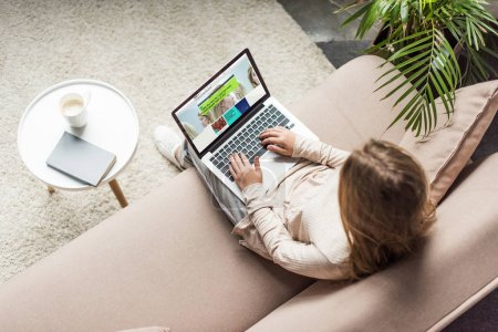 high angle view of woman at home sitting on couch and using laptop with bbc website on screen