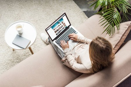 Photo for High angle view of woman at home sitting on couch and using laptop with amazon website on screen - Royalty Free Image