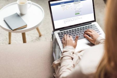 abgeschnittene Aufnahme einer Frau zu Hause, die auf der Couch sitzt und Laptop mit Facebook auf dem Bildschirm benutzt