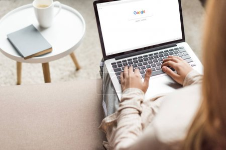 Photo for Cropped shot of woman at home sitting on couch and using laptop with google website on screen - Royalty Free Image