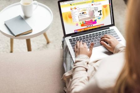 cropped shot of woman at home sitting on couch and using laptop with aliexpress website on screen