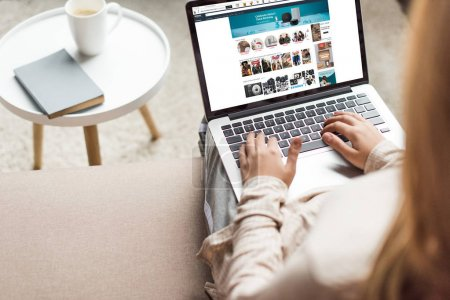 cropped shot of woman at home sitting on couch and using laptop with amazon website on screen