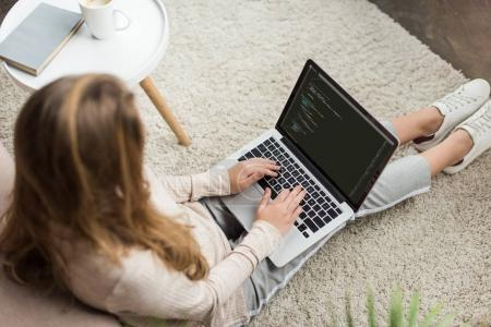 high angle view of young female developer coding with laptop at home