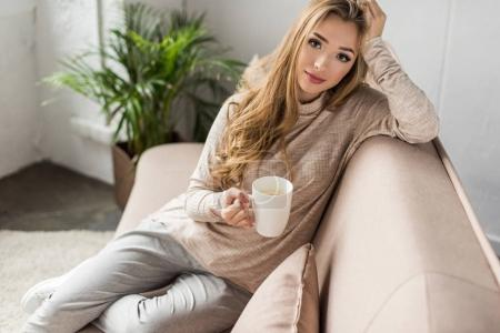 attractive young woman with cup of hot drink sitting on couch
