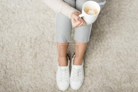 cropped shot of woman with cup of coffee sitting on floor