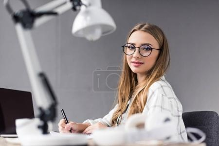 young beautiful student girl writing in notebook at workplace and looking at camera
