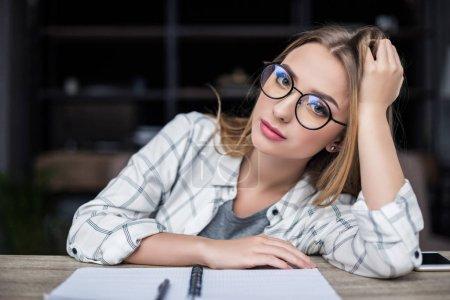 Foto de Chica joven studert cansado con notebook sentado en el lugar de trabajo y mirando a cámara - Imagen libre de derechos