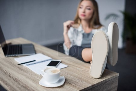 young businesswoman relaxing at workplace with feet on table