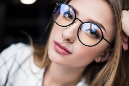 close-up portrait of beautiful young woman in eyeglasses looking at camera