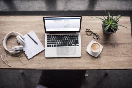 Photo pour Vue de dessus de standing ordinateur portable sur le lieu de travail modern avec facebook site Web sur l'écran - image libre de droit