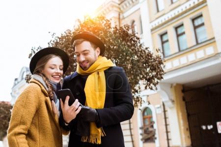 Photo pour Beau jeune couple en tenue d'automne regardant smartphone - image libre de droit