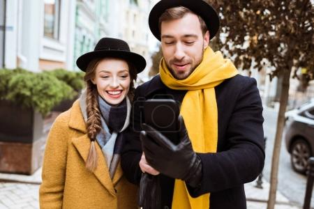 beautiful young couple in autumn outfit looking at smartphone